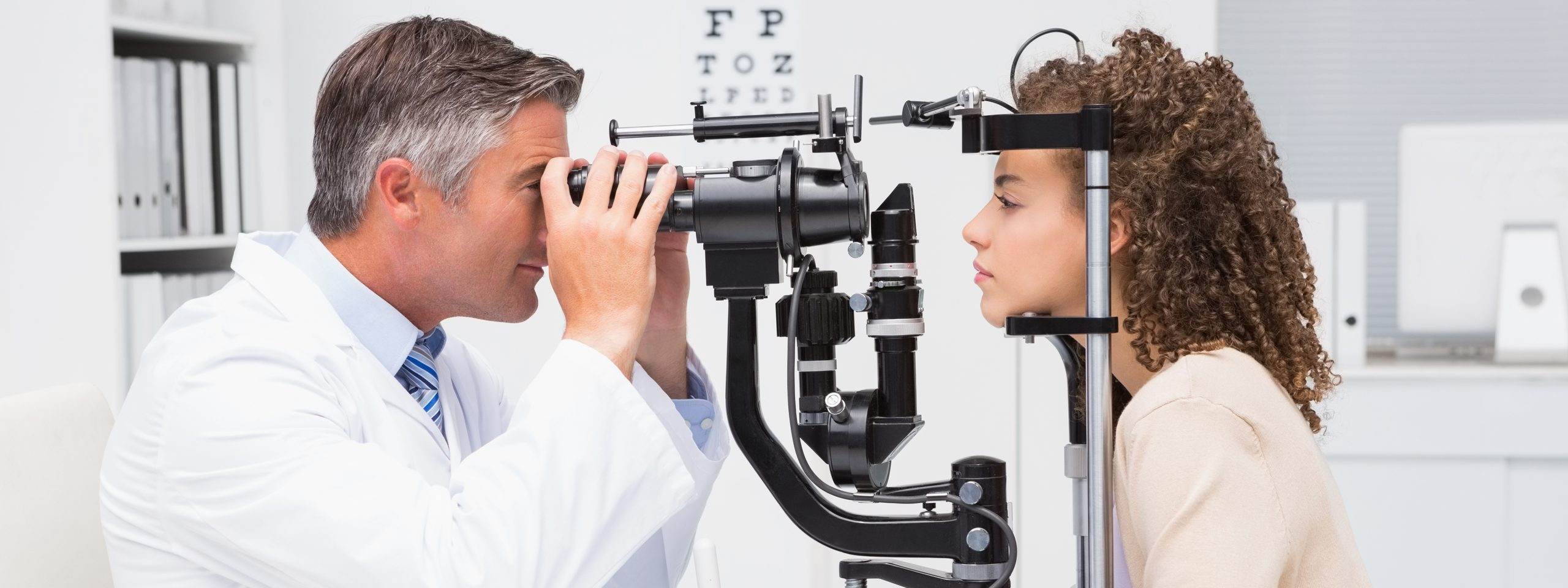 Male optometrist gives eye exam to female patient.