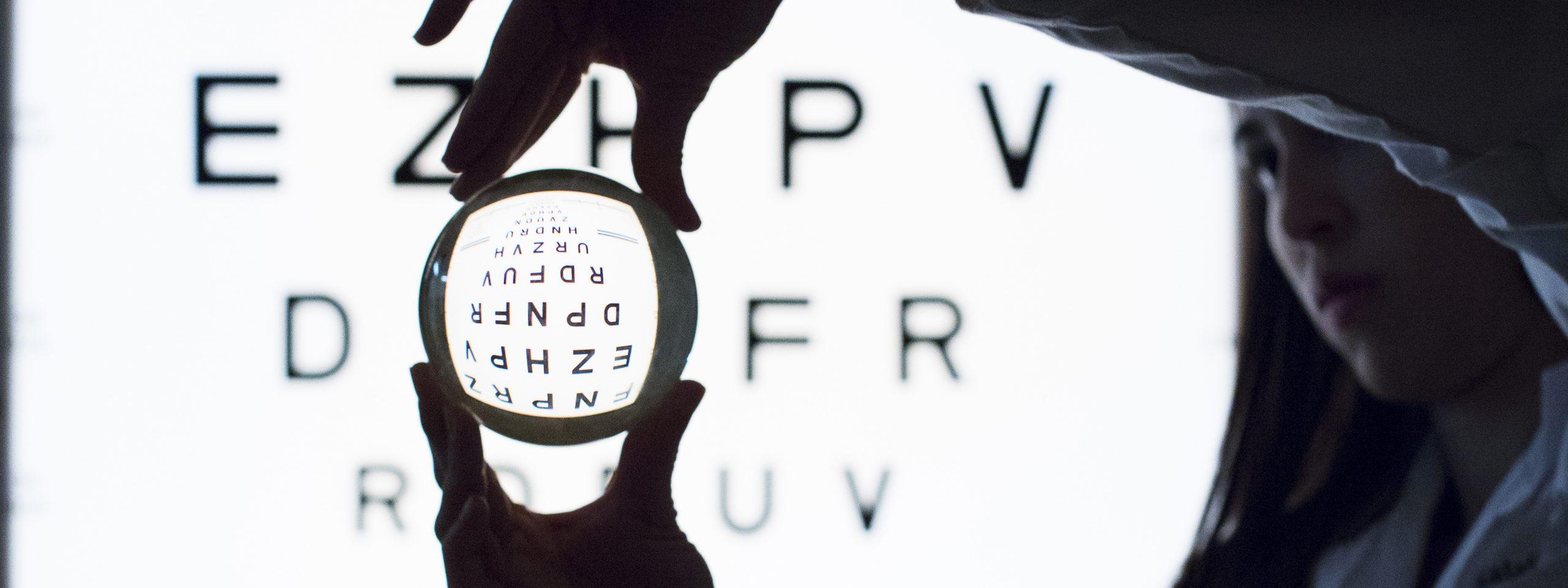 Female optometrist hold lens in front of illuminated eye chart.