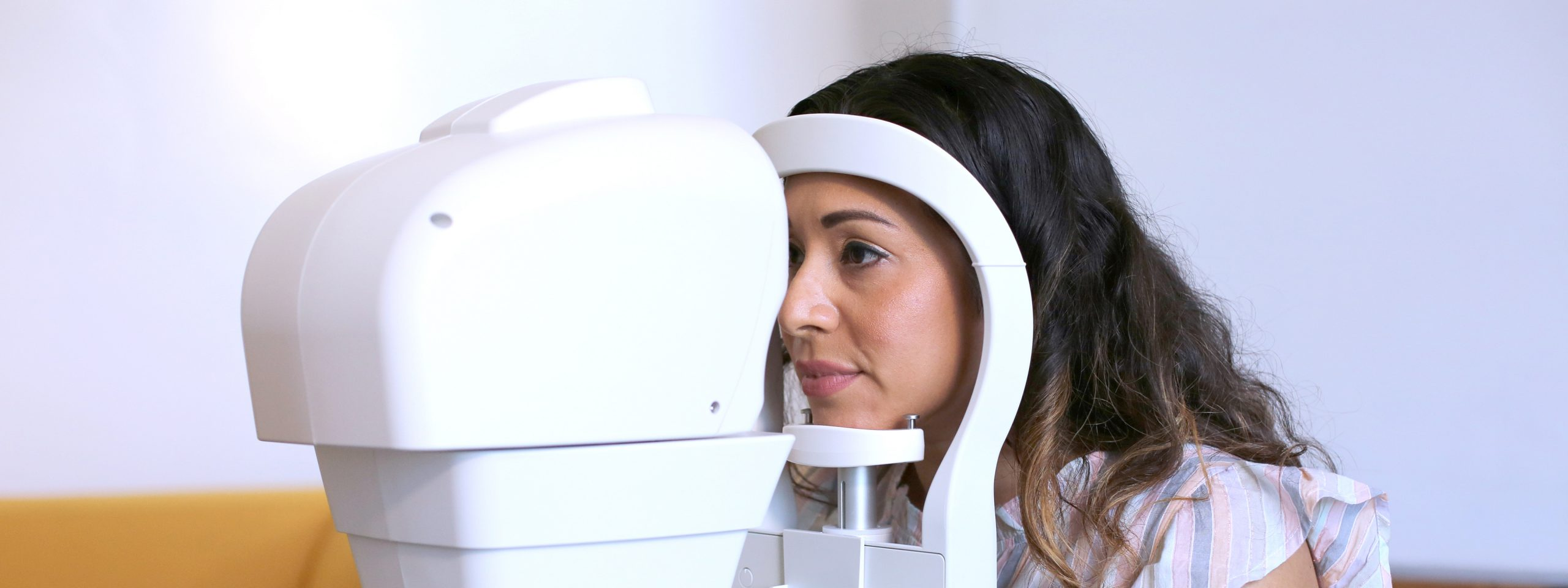female patient getting eye screened by a machine.