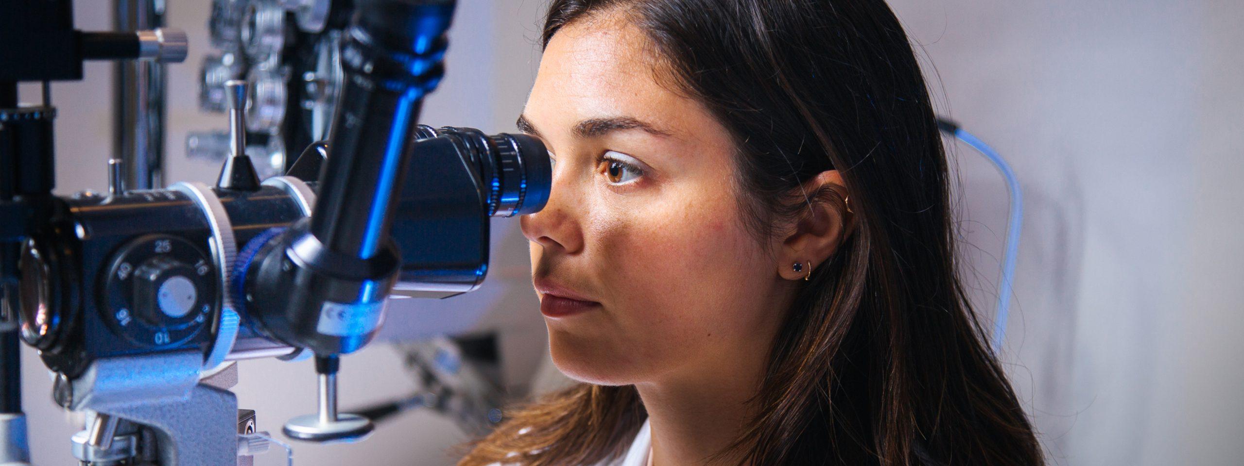 Female optometrist looks through lens